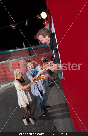 Teenagers Ordering Pizza from Food Truck stock photo, Happy teenagers served pizza from food truck owner by Scott Griessel