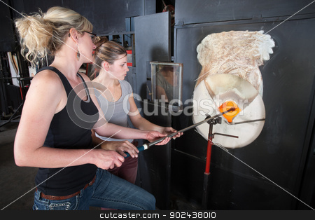 Two People Working at Blast Furnace stock photo, Young woman assisting glass art factory owner at kiln by Scott Griessel