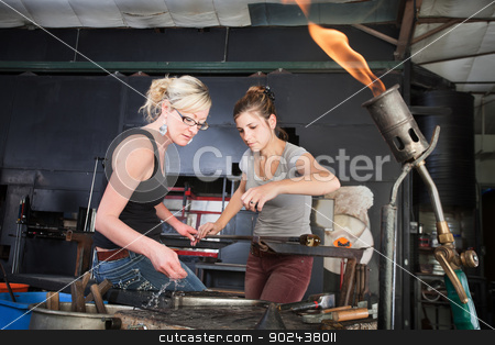 Workers Cleaning Tools stock photo, Worker helping woman clean iron tools at workbench by Scott Griessel
