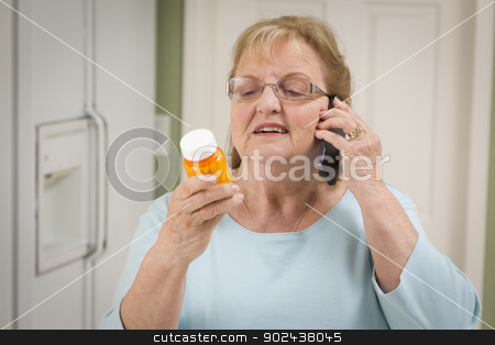 Senior Adult Woman on Cell Phone Holding Prescription Bottle stock photo, Beautiful Senior Adult Woman in Kitchen on Her Cell Phone Holding Prescription Bottle. by Andy Dean