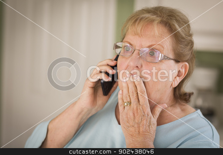 Shocked Senior Adult Woman on Cell Phone in Kitchen stock photo, Shocked Senior Adult Woman on Cell Phone with Hand Over Mouth in Kitchen. by Andy Dean