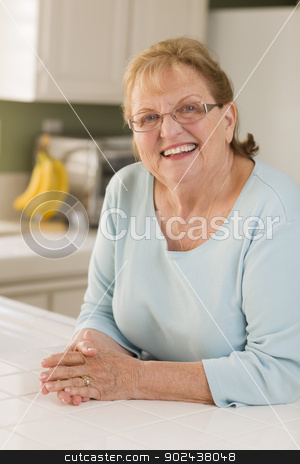 Portrait of Beautiful Senior Adult Woman in Kitchen stock photo, Portrait of a Beautiful Smiling Senior Adult Woman in Kitchen. by Andy Dean