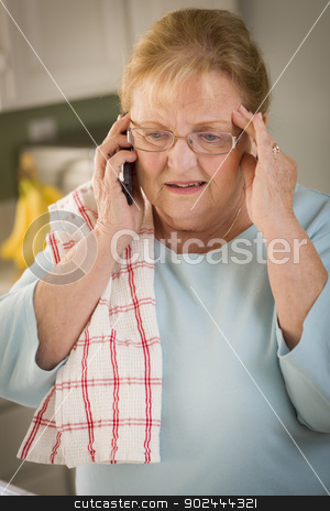 Shocked Senior Adult Woman on Cell Phone in Kitchen stock photo, Shocked Senior Adult Woman on Her Cell Phone in Kitchen. by Andy Dean