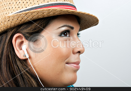 Woman Wearing Earbud Headphones stock photo, An attractive Hispanic woman listening to music playing through her stereo earbud headphones.  by Todd Arena