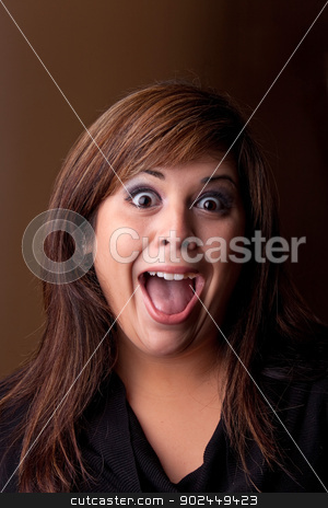 Crazy Girl Screaming stock photo, Woman with a funny look on her face smiles over a dark background. by Todd Arena