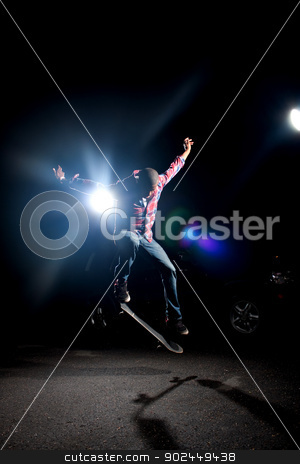 Cool Skateboarder Guy stock photo, A skateboarder performs tricks under dramatic rim lighting with lens flare.  by Todd Arena