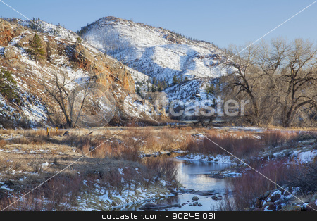 winter in mountain valley stock photo, winter in mountain valley in COlorado Rocky Mountains, with burned forest on slopes and North Fork of Cache la Poudre River by Marek Uliasz