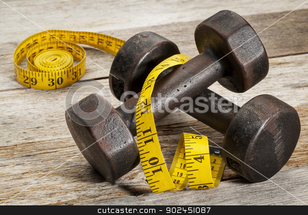 iron dumbbells and measuring tape stock photo, a pair of vintage iron rusty dumbbells with yellow measuring tape on white painted barn wood background - fitness concept by Marek Uliasz