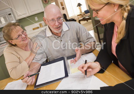 Senior Adult Couple Going Over Papers in Their Home with Agent stock photo, Senior Adult Couple Going Over Papers in Their Home with Agent. by Andy Dean