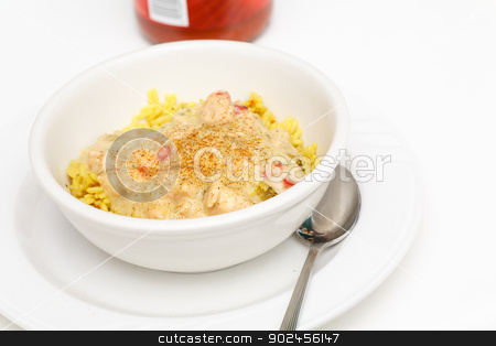 Chicken Chili on Yellow Rice stock photo, A white bowl of chicken chili over yellow rice garnished with cayenne pepper with hot sauce in background by Darryl Brooks