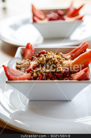 Two Bowls of Oatmeal in White Bowls stock photo, Steel-cut oatmeal in white bowl on white plate with strawberries, dried cranberries and walnuts by Darryl Brooks