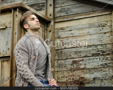 Attractive young man against rusty metal and wooden walls stock photo, Good looking guy leaning against rusty metal and wooden walls by Stefano Cavoretto