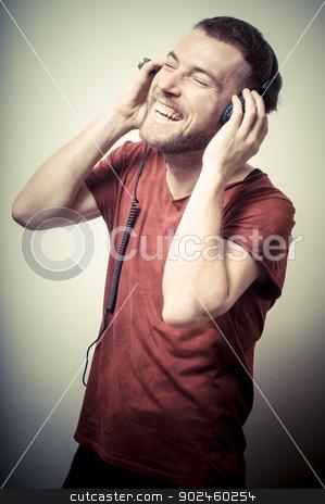 vintage portrait of fashion smiling guy with headphones stock photo, vintage portrait of fashion smiling guy with headphones on gray background by Eugenio Marongiu