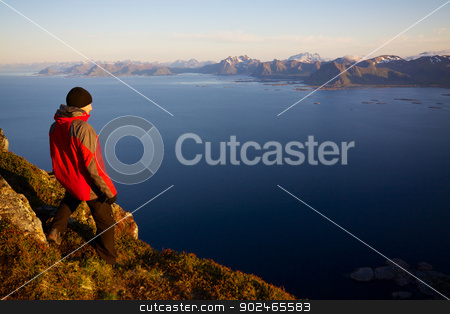 Hiking in Norway stock photo, Young man on the top of mountain Festvagtinden with picturesque scenery of chain of Lofoten islands, Norway by Harvepino