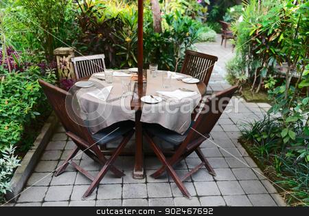 Outdoor cafe in a green garden stock photo, Summer outdoor cafe in a green garden by Iryna Rasko