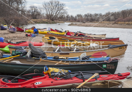 Kayaks and canoes stock photo, SOUTH PLATTE RIVER, EVANS, COLORADO - APRIL 6: Kayaks and canoes on a river shore during Annual All Club Paddle on April 6, 2013. It is a popular season opening paddling trip in northern Colorado. by Marek Uliasz