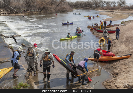 kayak and canoe portaging stock photo, SOUTH PLATTE RIVER, EVANS, COLORADO - APRIL 6: Portaging kayak and canoes over a river diversion dam during Annual All Club Paddle on April 6, 2013. It is a popular season opening paddling trip in northern Colorado. by Marek Uliasz