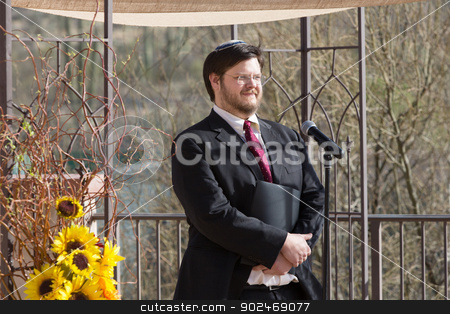 Smiling Bearded Rabbi stock photo, Smiling Caucasian Rabbi holding book by microphone by Scott Griessel
