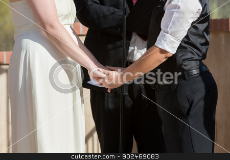 Women Holding Hands in Wedding Ceremony stock photo, Women holding hands in wedding ceremony outdoors by Scott Griessel
