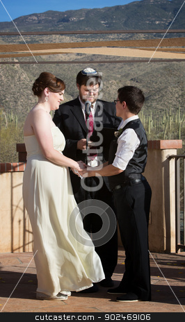 Rabbi with Gay Couple stock photo, Rabbi blessing lesbian marriage ceremony in desert by Scott Griessel