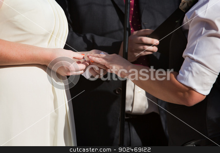 Putting Ring on Finger  stock photo, Woman putting ring on finger of partner in civil union by Scott Griessel