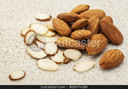 sliced raw almonds stock photo, sliced and whole raw almonds on a white painted rough wood barn background by Marek Uliasz