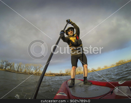 paddling stand up board stock photo, mature male paddler enjoying workout on stand up paddleboard (SUB), calm lake in Colorado, early spring by Marek Uliasz
