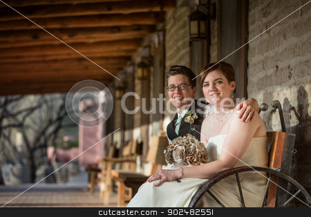 Smiling Newlyweds Sitting stock photo, Smiling same sex married partners sitting together by Scott Griessel