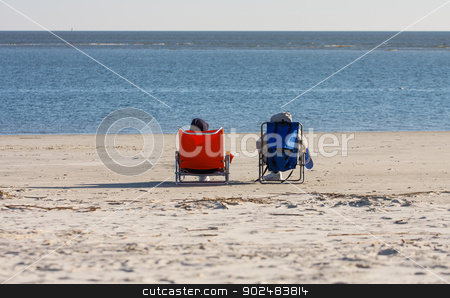 Orange and Blue Chairs on Beach stock photo, Two people resting in orange and blue beach chairs by Darryl Brooks