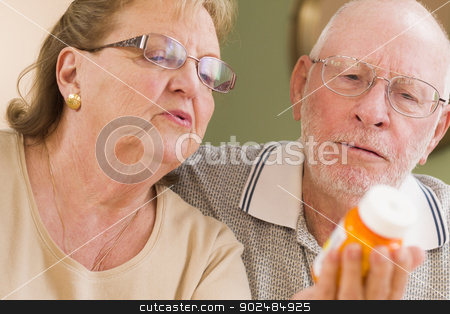 Senior Couple Reading Medicine Bottle stock photo, Curious Senior Couple Reading Prescription Medicine Bottle Together. by Andy Dean