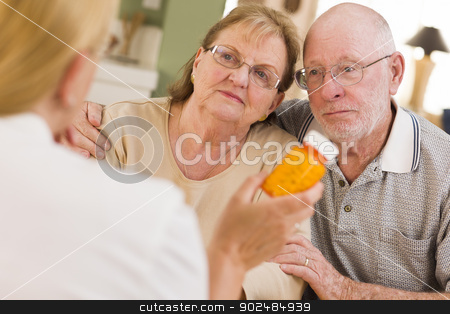 Doctor or Nurse Explaining Prescription Medicine to Senior Coupl stock photo, Doctor or Nurse Explaining Prescription Medicine to Attentive Senior Couple. by Andy Dean