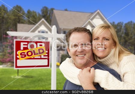 Couple in Front of Sold Real Estate Sign and House stock photo, Happy Couple Hugging in Front of Sold Real Estate Sign and House. by Andy Dean