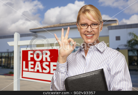 Businesswoman In Front of Office Building and For Lease Sign stock photo, Smiling Businesswoman with Okay Sign In Front of Vacant Office Building and For Lease Real Estate Sign. by Andy Dean