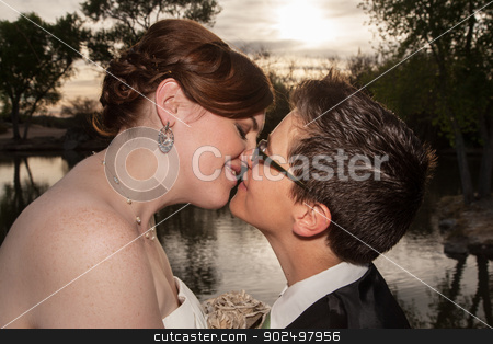 Kissing Married Gay Couple stock photo, Two kissing newlywed lesbians outside near pond by Scott Griessel