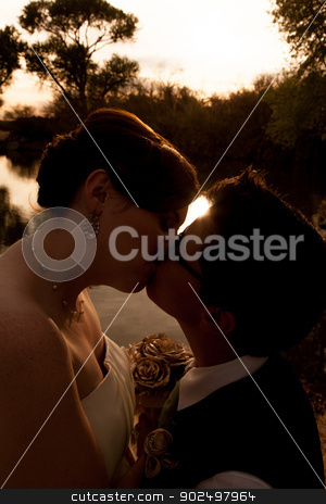 Female Gay Couple Kissing stock photo, Romantic lesbian couple kissing near sunset outdoors by Scott Griessel