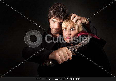 Dagger At Neck stock photo, Scary man threatens witch with sharp athame knife by Scott Griessel