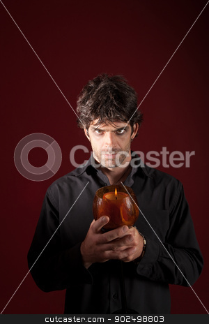 Wizard Holding Candle stock photo, Wizard holds candle with both hands over maroon background by Scott Griessel