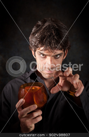 Warlock With Candle stock photo, Warlock holds candle over dark colored background by Scott Griessel