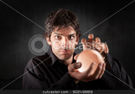 Male Fortune Teller stock photo, Serious fortune teller holds crystal ball over maroon background by Scott Griessel
