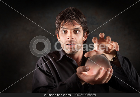 Fortuneteller With Crystal Ball stock photo, Fortuneteller gazes crystal ball over maroon background by Scott Griessel