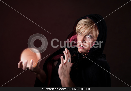 Surprised Fortuneteller stock photo, Caucasian female fortuneteller wearing black viel holds crystal ball over maroon background by Scott Griessel