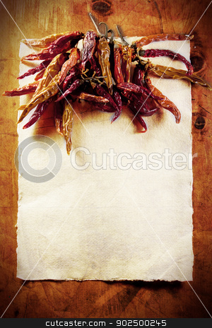 Dried peppers frame stock photo, Dried peppers border on a vintage paper background on an old wooden table. Plenty of copyspace–perfect for a themed restaurant menu or a preserve label. by Piccia Neri
