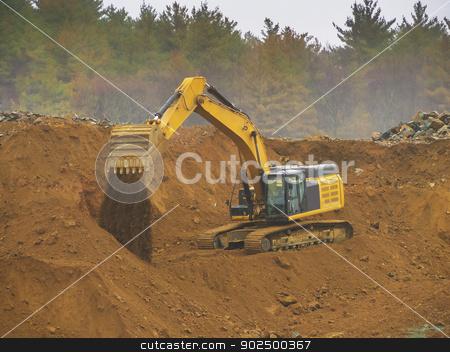 Excavator shovel stock photo, Excavator shovel digging in a gravel pit by Christian Delbert