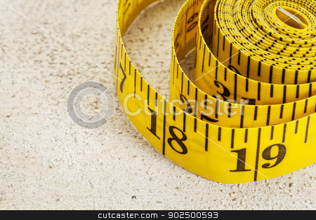 tape measure stock photo, yellow inch tape measure on a rough white painted barn wood background by Marek Uliasz