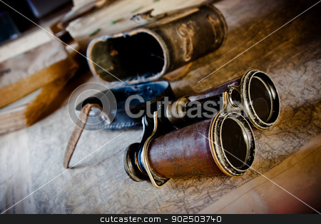 Vintage binoculars: planning an expedition stock photo, Old binoculars on an old map: an explorer planning the next expedition. by Piccia Neri