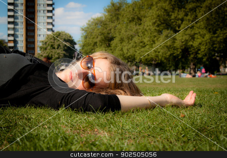Sleeping beauty stock photo, Beautiful young woman snoozing in an urban park in the spring. by Piccia Neri