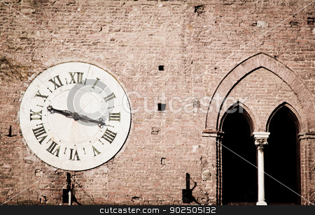 Ancient wall clock stock photo, Ancient wall clock on the outside of a medieval palace in Siena, Italy, that used be a hospital and is now a museum.  by Piccia Neri