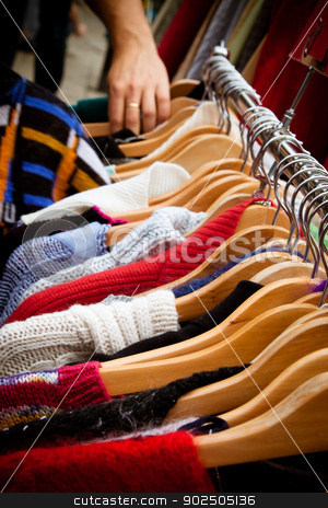 Rack of jumpers at market stock photo, A rack of second-hand jumpers and cardigans at a market in London: recession bargains. Hand of someone browsing visible in the background. by Piccia Neri
