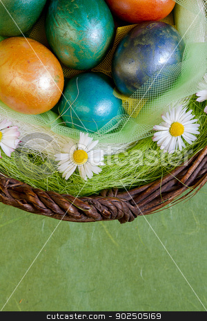 Basket of Easter eggs stock photo, Detail of basket of colorful decorated Easter eggs with daisy flowers, against a green background. Plenty of copy space. by Piccia Neri