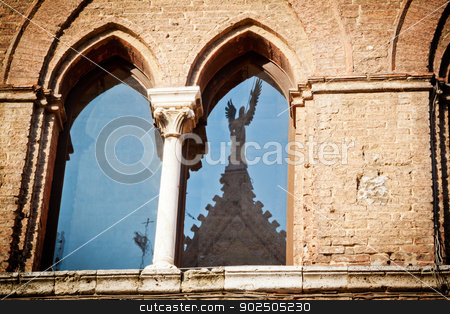 Medieval window in Siena stock photo, The window of a medieval palace in Siena (Santa Maria della Scala) opposite the cathedral, with the stature of an angel reflected on the glass. by Piccia Neri